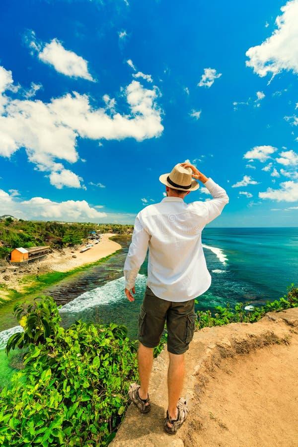 Happy travel man with hat enjoying summer vacation on tropical island Bali and enjoy amazing top view tropical Balangan beach stock photography