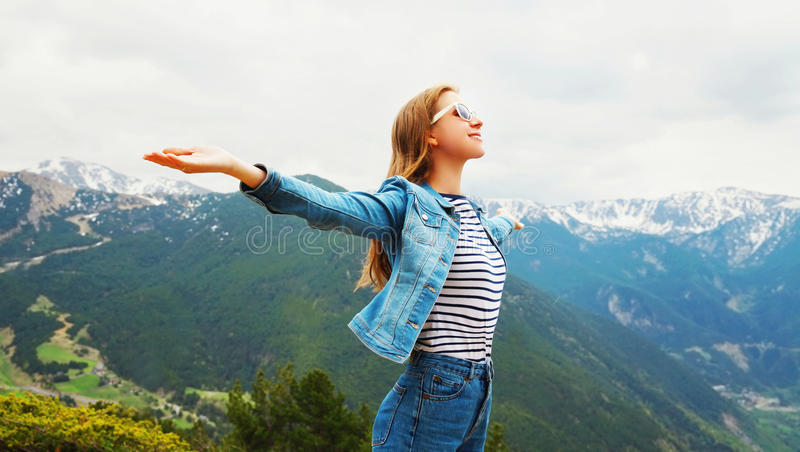 Happy travel woman enjoys fresh air mountains raises hands up. Over view landscape Spain background royalty free stock images