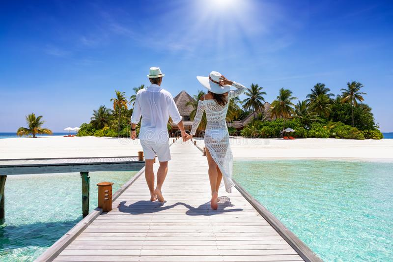 Couple walks down a wooden pier in the Maldives, Indian Ocean. A happy traveler couple in white summer clothing walks down hand in hand a wooden pier towards a royalty free stock image