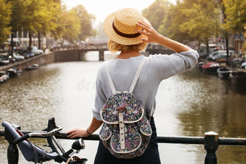 Happy traveler girl enjoying Amsterdam city. Tourist woman looking to the Amsterdam canal, Netherlands, Europe royalty free stock images
