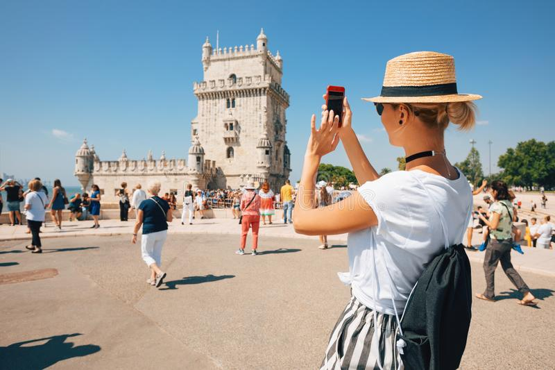 Happy traveler girl in Lisbon near Belem Tower. Tourist woman taking picture of Belem Tower, Portugal royalty free stock images