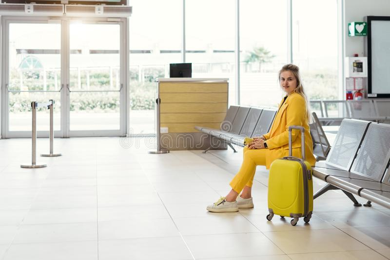 Happy traveler going to the gates, flight in airport. Happy traveler waiting near gates, flight in airport. Woman with yellow suitcase from the back in waiting royalty free stock photo