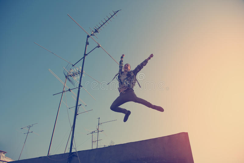 Happy traveler jumping on the roof in city stock image