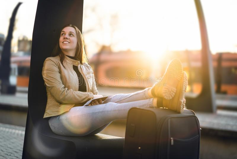 Happy traveler keeping legs and shoes on suitcase. stock images