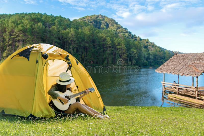 Happy traveler lifestyle women on vacation camping with tents playing guitar in the forest near river. stock photography