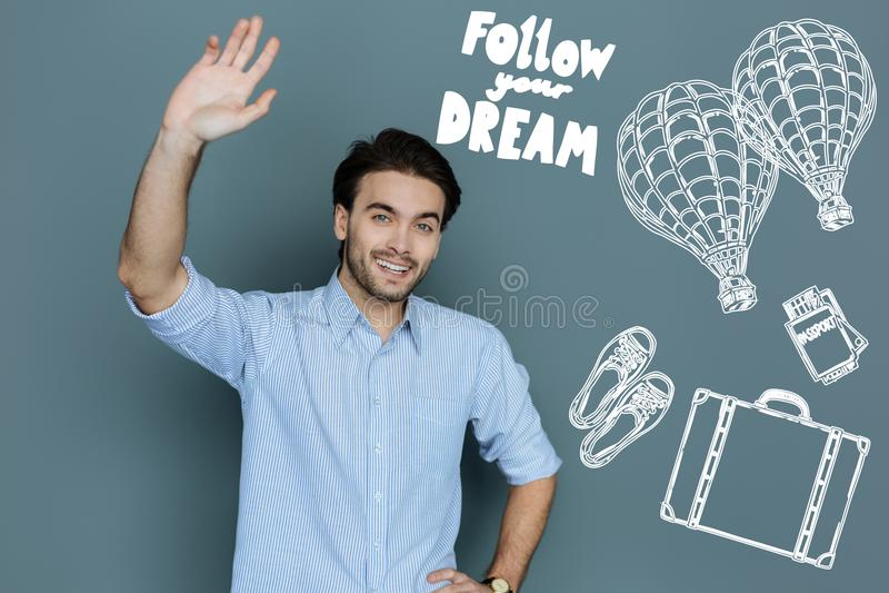 Happy traveler waving his hand and smiling cheerfully royalty free stock photos