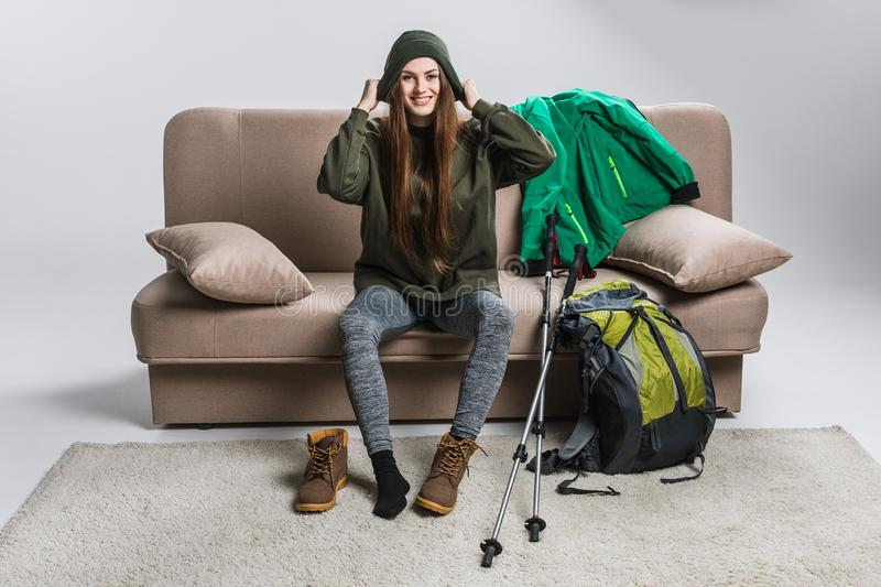 Happy traveler wearing hat and hiking boots on sofa. With backpack royalty free stock images