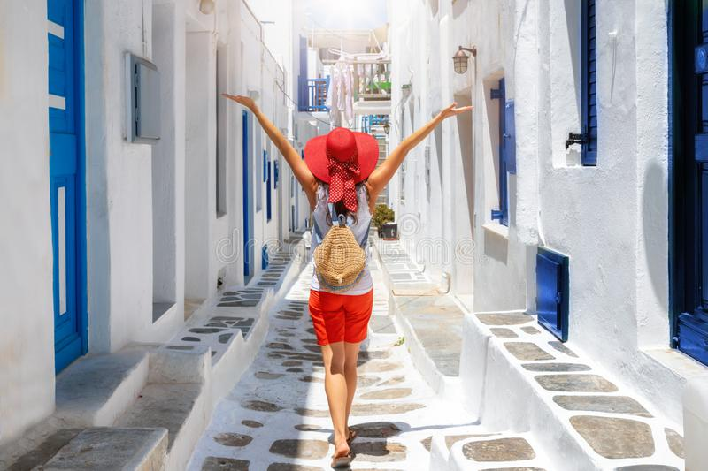 Woman walks through the white and blue streets of the Cyclades islands of Greece royalty free stock images