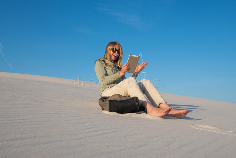 Happy traveler, young woman sits alone in the beach royalty free stock photography