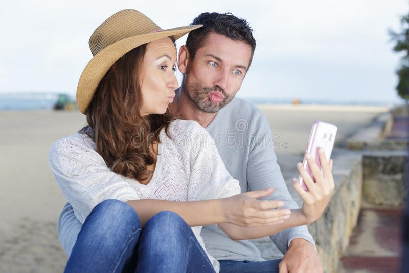 Happy traveling couple in love taking selfie on phone stock photos