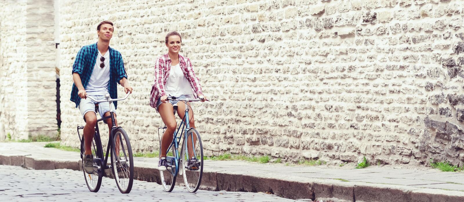 Young couple of hipsters riding a bicycle. Date in old town. Love, relationship, romance concept. royalty free stock photos