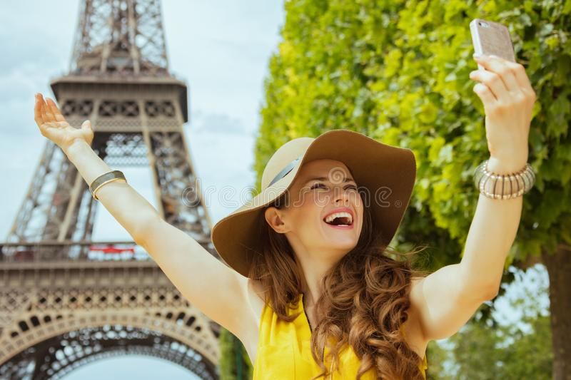 Happy traveller woman rejoicing and taking selfie with phone. Happy trendy traveller woman in yellow blouse and hat rejoicing and taking selfie with cellphone royalty free stock photography