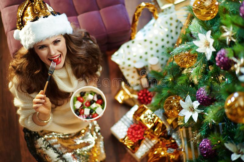 Happy trendy housewife eating healthy salad near Christmas tree stock photography