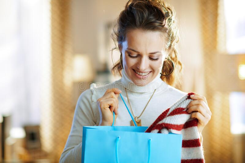 Happy woman with blue shopping bag checking purchased sweater stock images