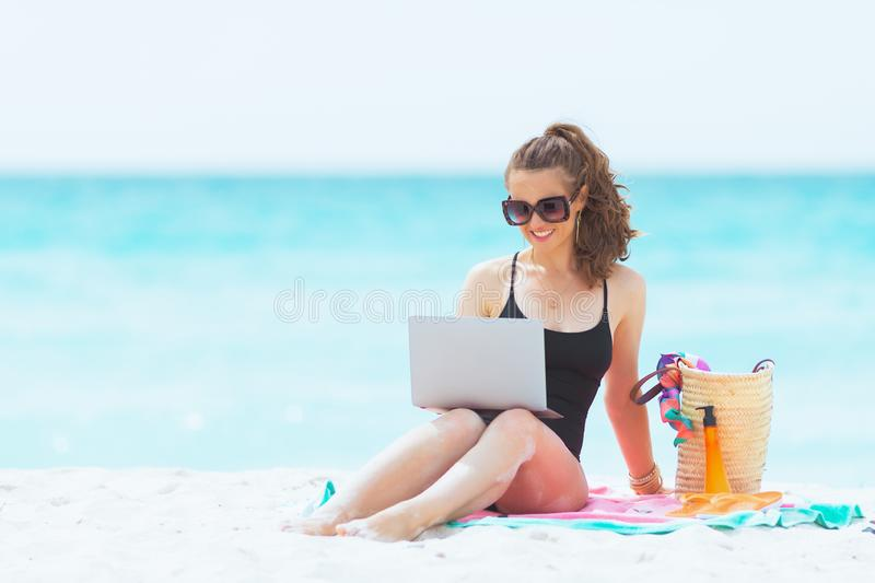 Happy trendy middle age woman on white beach with laptop royalty free stock photos