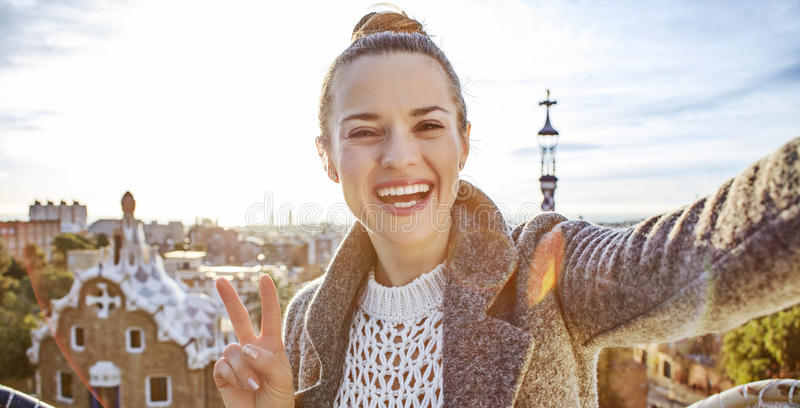 Happy trendy tourist woman in Barcelona, Spain taking selfie. Barcelona signature style. happy trendy tourist woman in coat in Barcelona, Spain taking selfie stock photography
