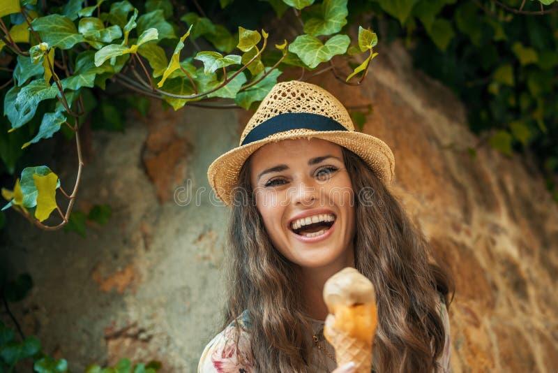 Happy trendy tourist woman in Pienza, Italy eating ice cream stock photography
