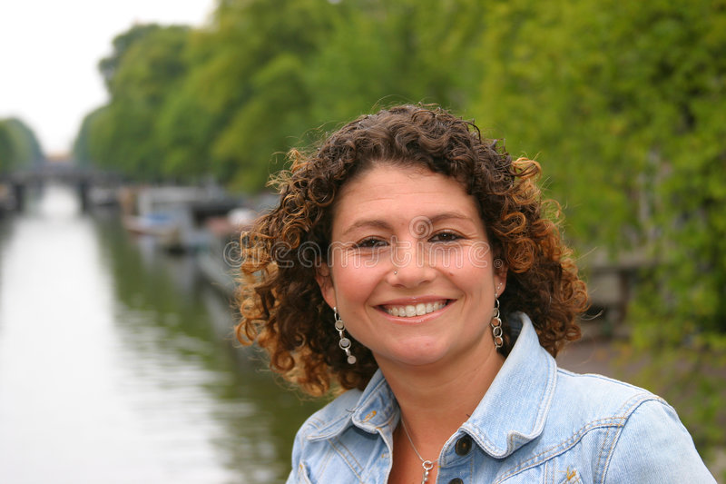 Happy tunisian woman. In front of canals in amsterdam stock photo