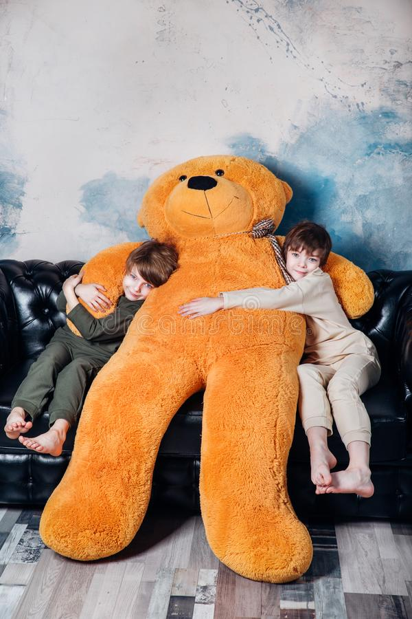Happy twin brothers in pajamas hugging big teddy bear soft toy happy smiling at home royalty free stock photography