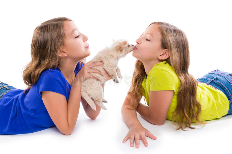 Happy twin sister kid girls kissing puppy dog lying royalty free stock image