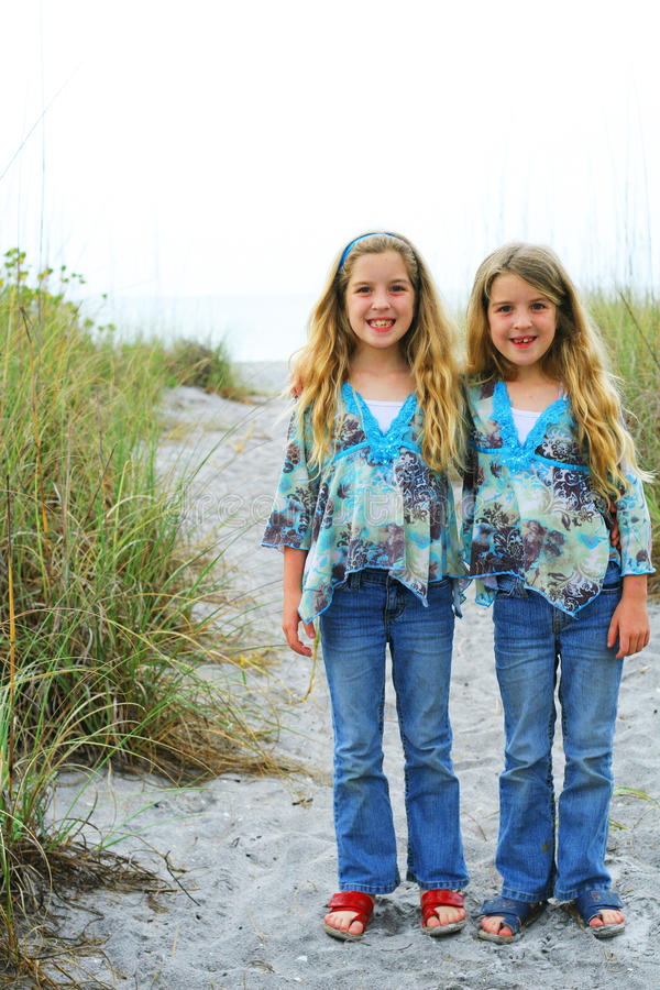 Happy twin sisters on the beach vertical