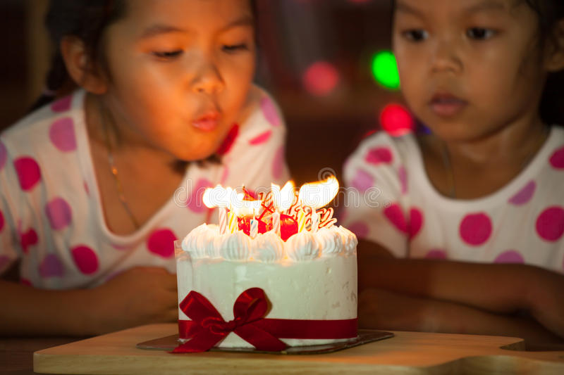 Happy twin two asian little girls blowing candles on birthday cake. Happy twin two asian little girls celebrating birthday and blowing candles on birthday cake stock image