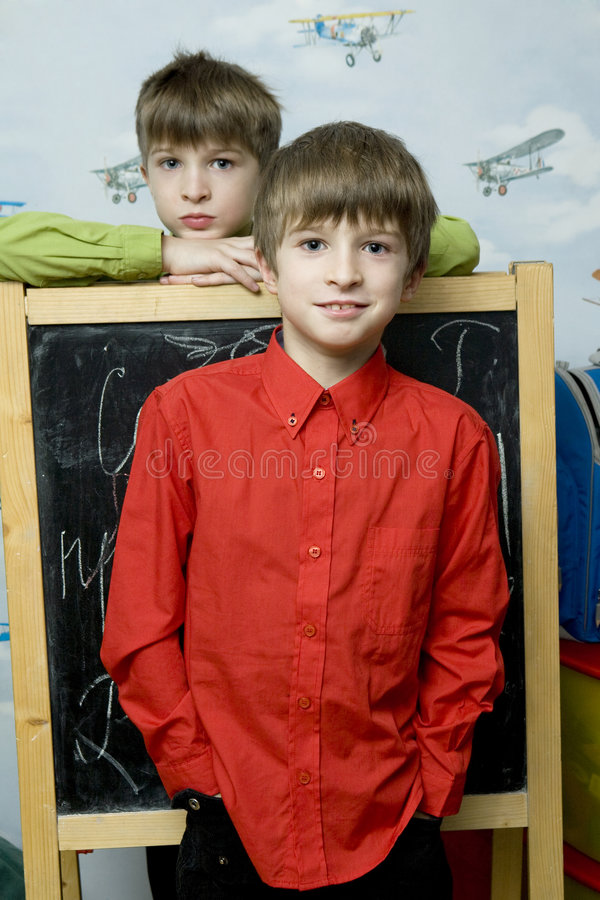 Happy twins brothers standing at wall. Wallpaper with airplane royalty free stock images
