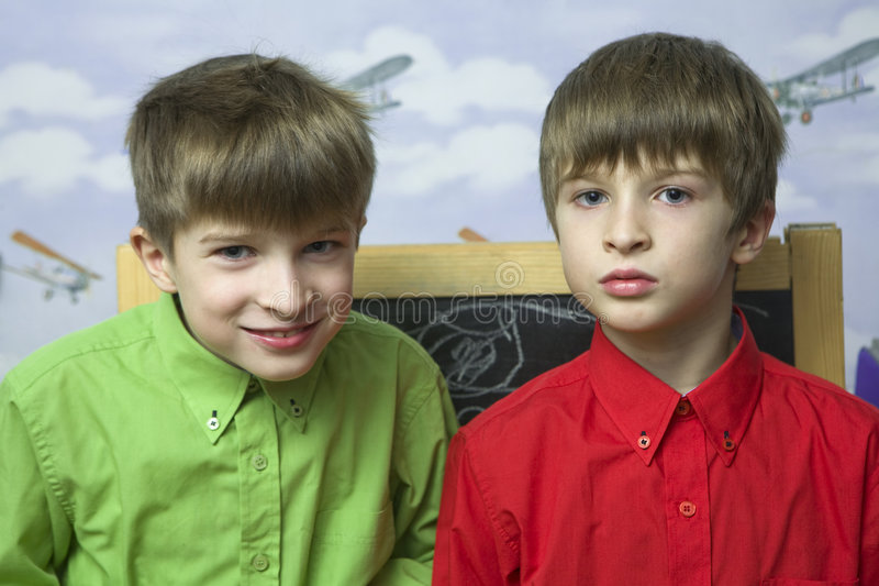 Happy twins brothers standing at wall. Wallpaper with airplane stock photos