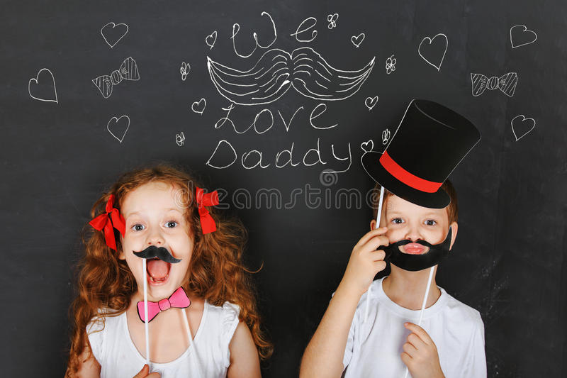 Happy twins kids hold carnival mustache and beard, father day co stock photography