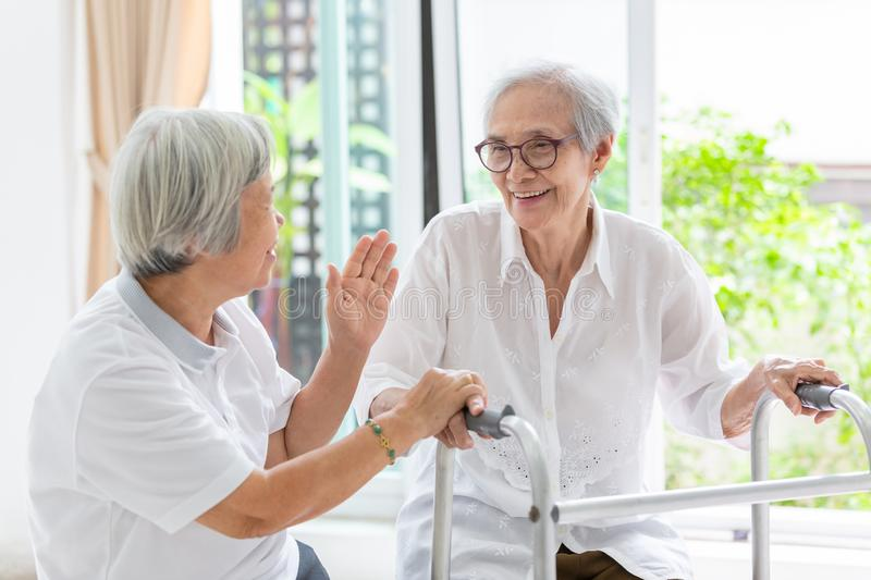 Happy two asian senior women friends holding hands for care,support and fun talking,time together,old people smiling with walker stock image