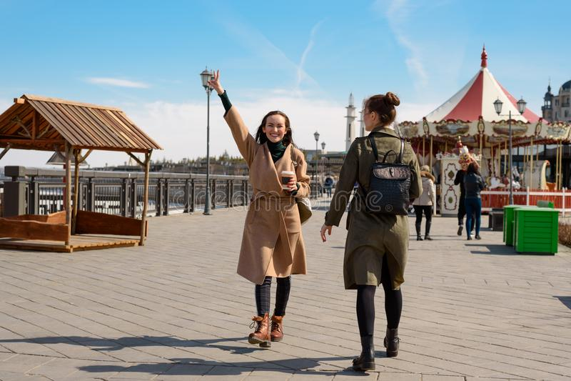 Happy two female students of a friend walk around the city in stylish coats and backpacks and drink coffee from disposable cups, a royalty free stock image