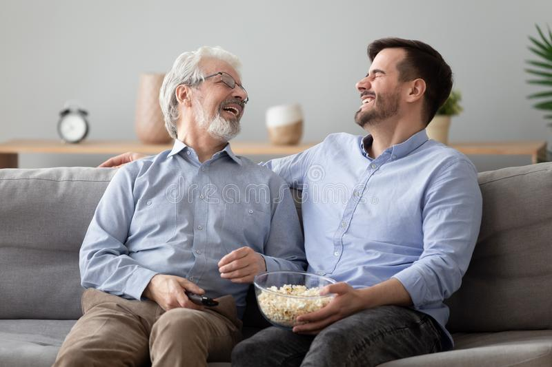 Happy two generations male family laugh enjoy talk watching television. Happy two generations male family laugh enjoy talk watching funny comic tv show, cheerful royalty free stock photo