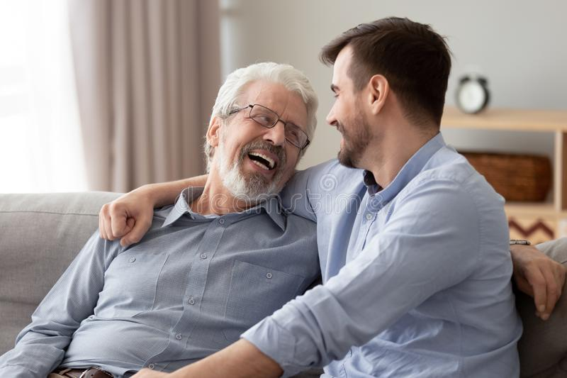 Happy two generations male family laugh talking bonding on sofa. Happy two generations male family laugh enjoy talking bonding embracing sit on sofa at home, old stock images