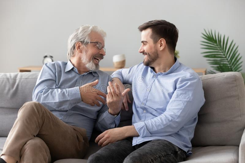 Happy old father and young son talking sit on sofa. Happy two generations male family, old senior mature father and smiling young adult grown son enjoying stock photography