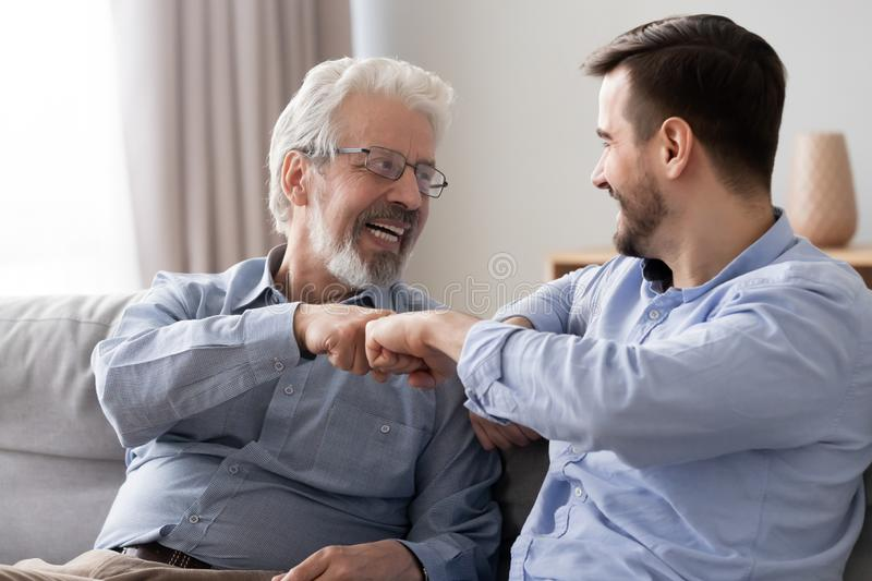 Happy old father and young son laughing giving fist bump. Happy two generations men family old elder father and adult grown son laughing giving fist bump sit on stock photos