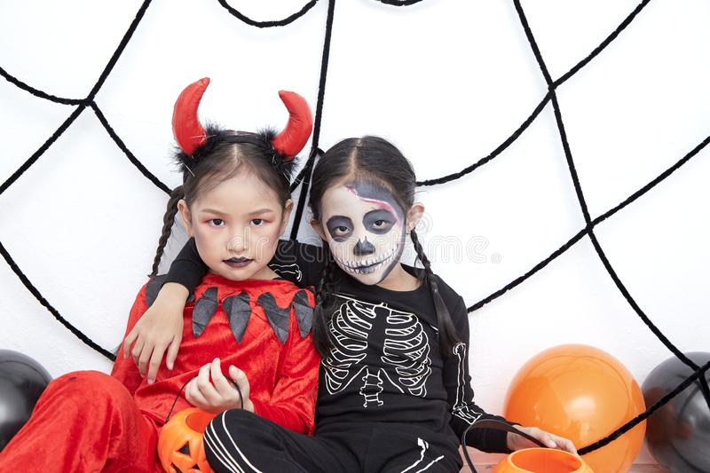 Happy two sisters on Halloween party. Happy two little asian girls sitting in room decorated for Halloween day royalty free stock photos