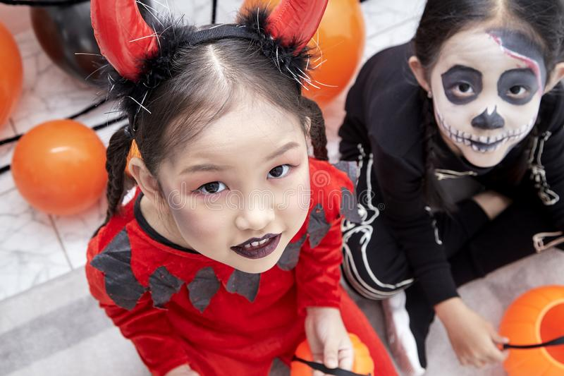 Happy two sisters on Halloween party. Happy two little asian girls sitting in room decorated for Halloween day stock images