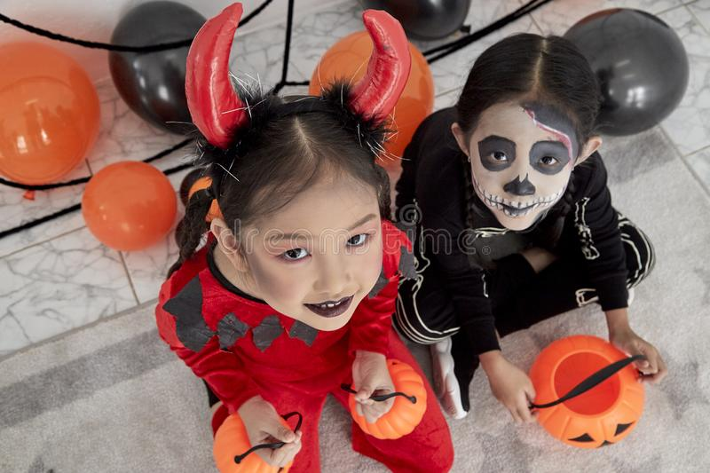 Happy two sisters on Halloween party. Happy two little asian girls sitting in room decorated for Halloween day royalty free stock photo