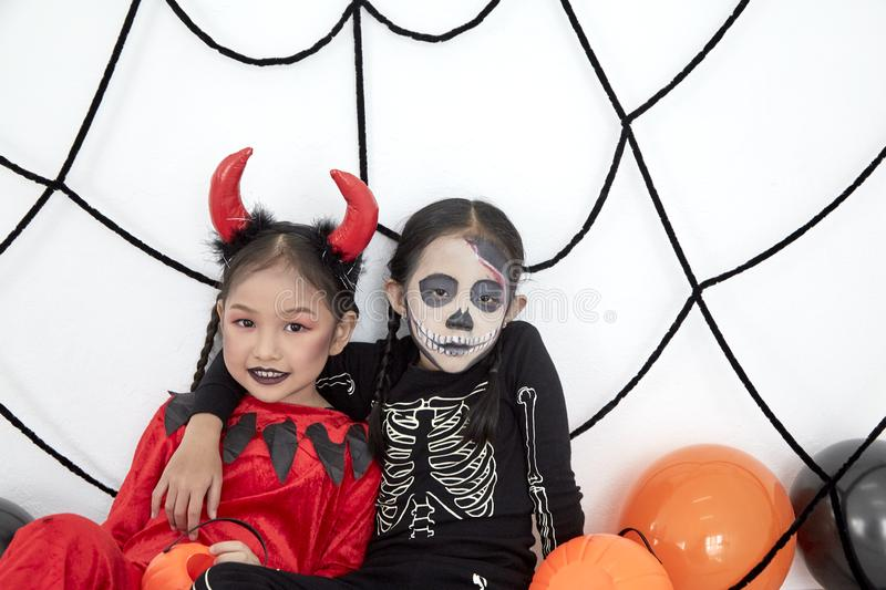 Happy two sisters on Halloween party. Happy two little asian girls sitting in room decorated for Halloween day stock photography