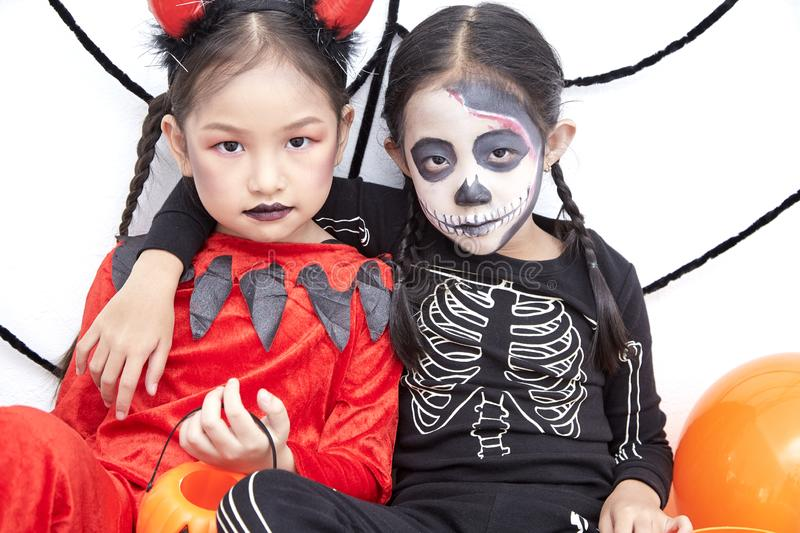 Happy two sisters on Halloween party. Happy two little asian girls sitting in room decorated for Halloween day stock photos