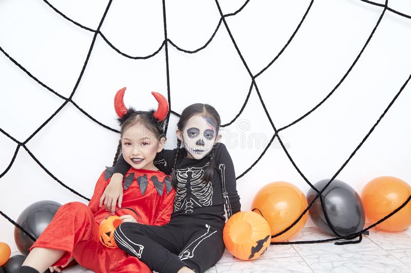 Happy two sisters on Halloween party. Happy two little asian girls sitting in room decorated for Halloween day stock image