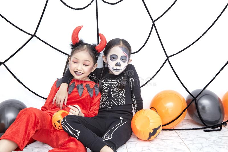Happy two sisters on Halloween party. Happy two little asian girls sitting in room decorated for Halloween day stock photo
