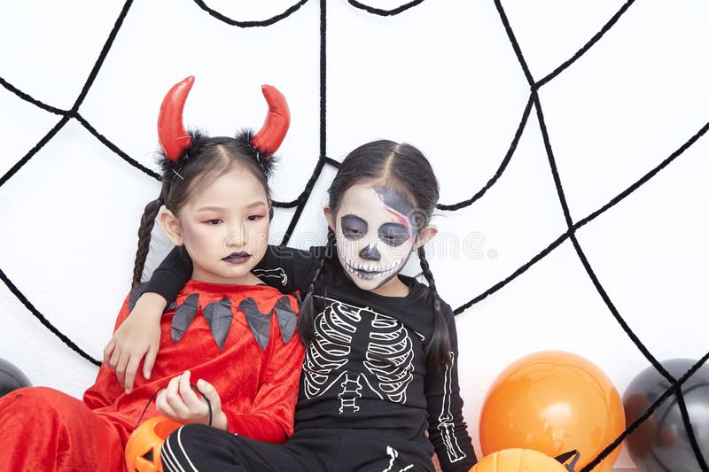 Happy two sisters on Halloween party. Happy two little asian girls sitting in room decorated for Halloween day royalty free stock photography