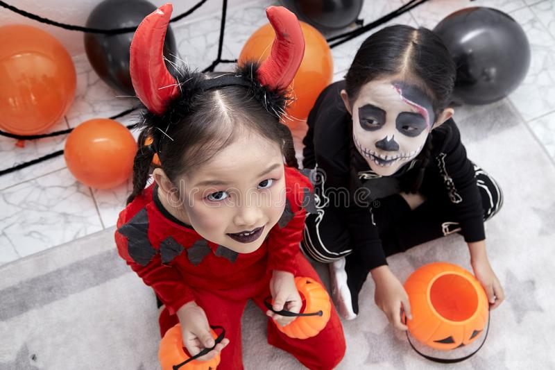 Happy two sisters on Halloween party. Happy two little asian girls sitting in room decorated for Halloween day royalty free stock image