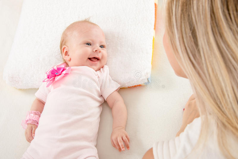 Happy two-month girl looking at mother. A two-month baby lying on his back on the bed, sitting next to the child and mother looking at her royalty free stock photography