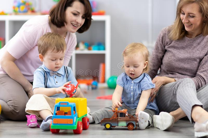 Happy two mothers with their children play at home interior stock photos