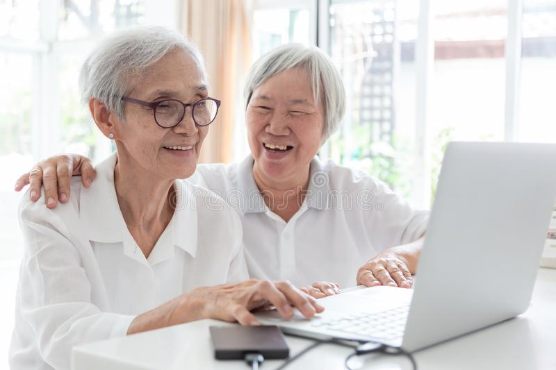 Happy two senior asian woman,sisters or friends talking and enjoying using laptop computer together at home,smiling elderly people royalty free stock images
