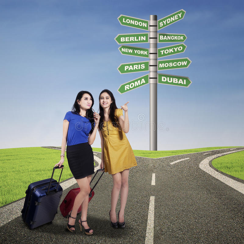 Happy two woman friends with suitcases royalty free stock photo