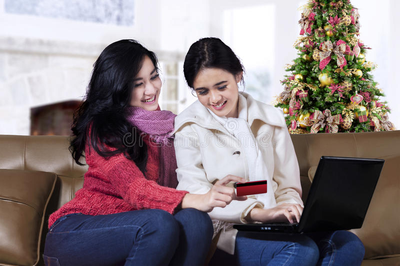 Happy two woman shopping online. Happy two young women shopping online with laptop near Christmas tree stock photo
