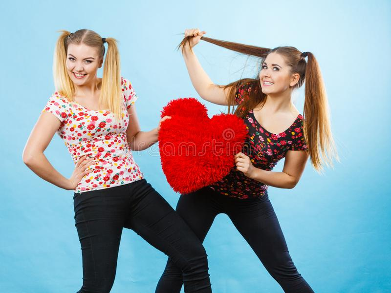 Happy two women holding heart shaped pillow royalty free stock photography